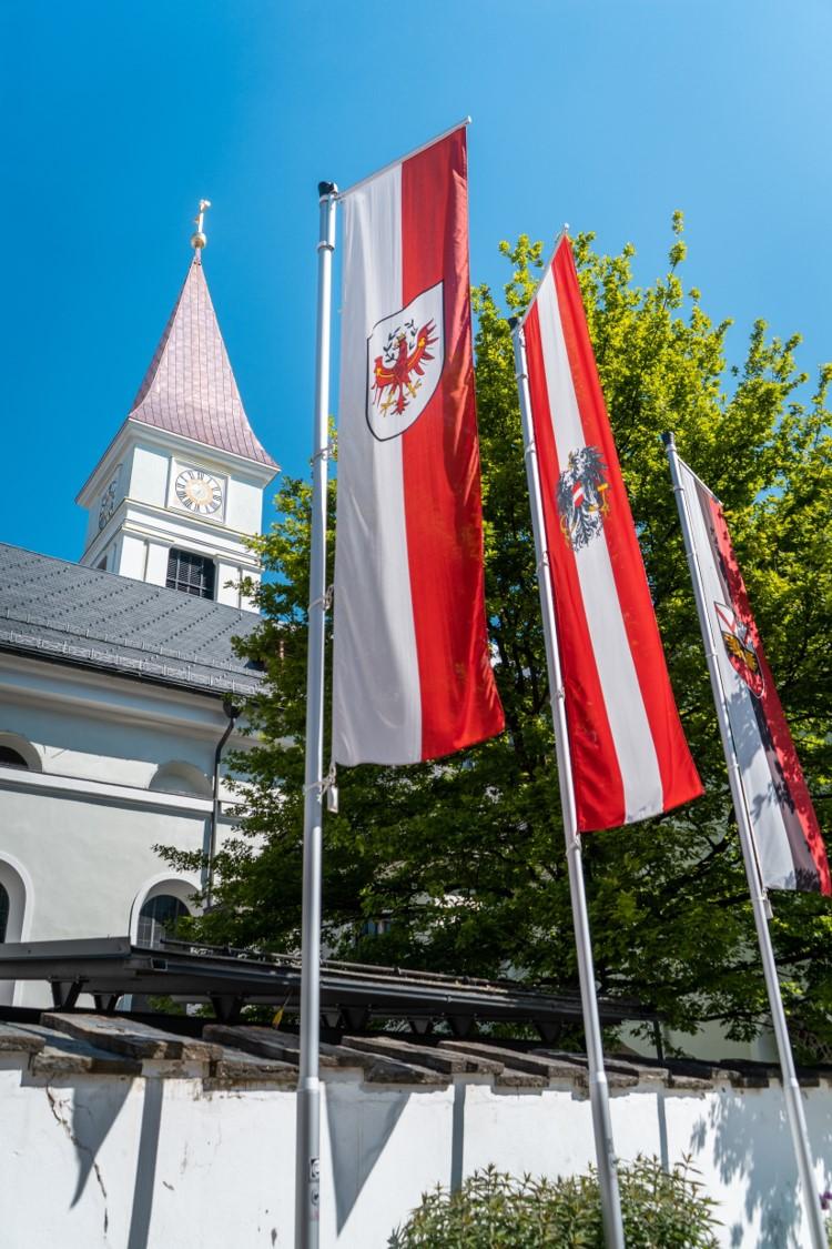 Beflaggung und Kirchturm im Hintergrund